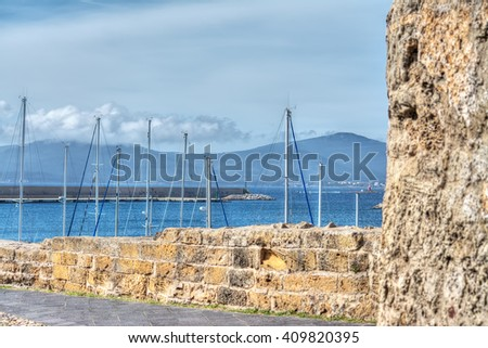 defensive wall and tower by Alghero promenade - stock photo