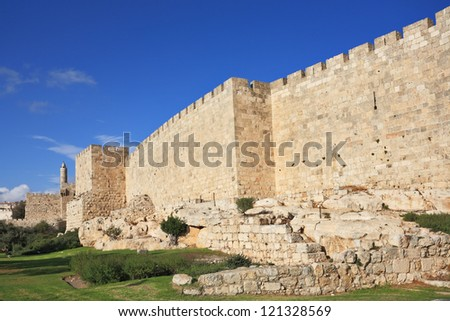 Defensive wall of the ancient holy Jerusalem, lit by the bright sun. Wonderful green lawn - stock photo