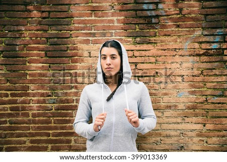 Defiant urban fitness woman portrait. City sport motivation. Female confident athlete outside in the street. - stock photo