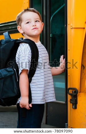 Defiant young boy in front of yellow school bus waiting to board on first day back to school. - stock photo