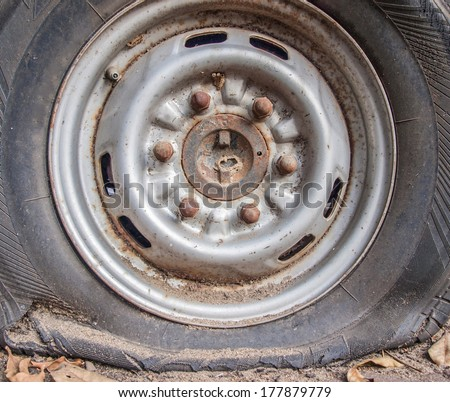 Deflated damaged tyre on car wheel. - stock photo