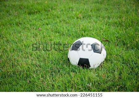Deflated soccer ball on grass - stock photo