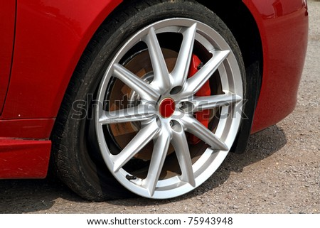 Deflated tyre damage to car wheel - stock photo