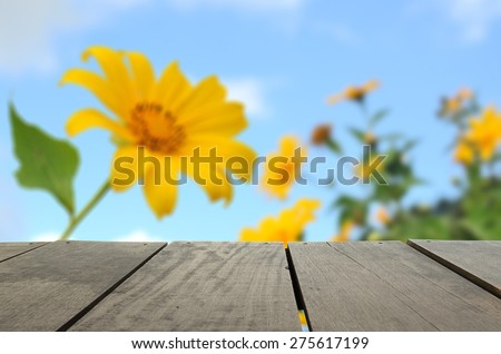 Defocus and blur image of terrace wood and Beautiful landscape with sunflower field over cloudy blue sky and bright sunlights for background usage - stock photo