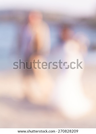 Defocus couple kissing on the beach , abstract blur background for card design, blurred wallpaper and illustration. - stock photo
