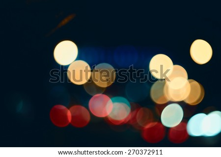 Defocused abstract lights street background. Festive Lights Bokeh Street Lights. Abstract background spherical bokeh of car lights in the hight. Instagram color style. - stock photo