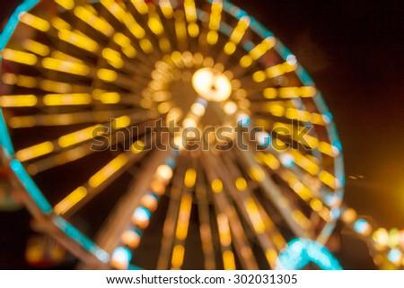 Defocused and blur image of Amusement park at night - ferris wheel and rollercoaster in bokeh - stock photo