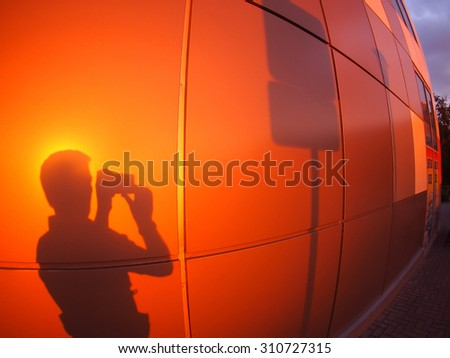 Defocused and blur image of  man's silhouette on a red-orange wall, who photographs a road sign in the evening at sunset with wide angle fisheye lens and distortion view - stock photo