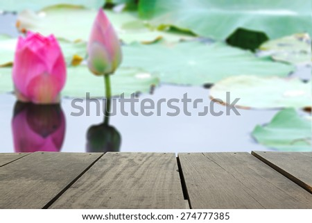 Defocused and blur image of terrace wood and Pink fresh lotus bud flower in pond for background usage - stock photo