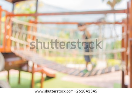 Defocused and blur image of young boy try to cross the bridge in  children's playground at public park for background usage. - stock photo