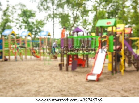 Defocused and blurred image for background of children's playground, activities at public park. Child swings on modern kids playground. Colorful playground on yard in the park - stock photo