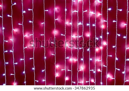 Defocused and blurred image of a bright red wall with white lights on the white wires vertical rows. - stock photo
