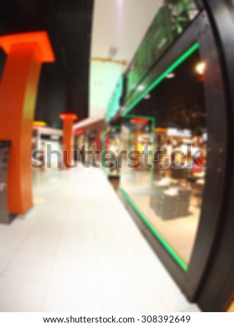 Defocused and blurred image of a large shopping mall hall with glass cases and columns with wide angle fisheye lens and distortion view. The image was blurry for use as background - stock photo