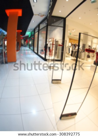 Defocused and blurred vertical image of a large shopping mall hall with glass cases and columns with wide angle fisheye lens and distortion view. The image was blurry for use as background - stock photo