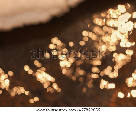 Defocused and golden light spots on water of lake