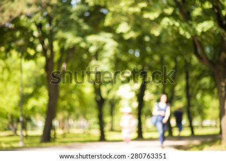 Defocused background of park in spring or summer season, blurred people walking,  - stock photo