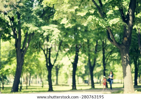 Defocused background of park in spring or summer season, blurred people walking, retro colors - stock photo