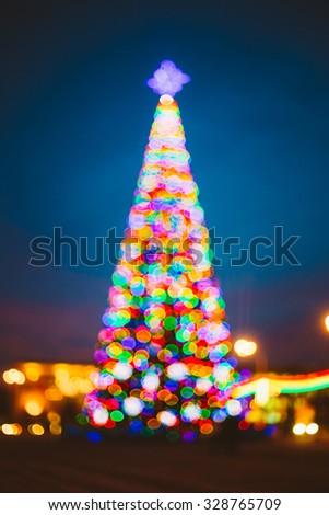 Defocused Blue Bokeh Background Effect. Design Backdrop. New Year Boke Lights Xmas Christmas Tree And Festive Illumination - stock photo