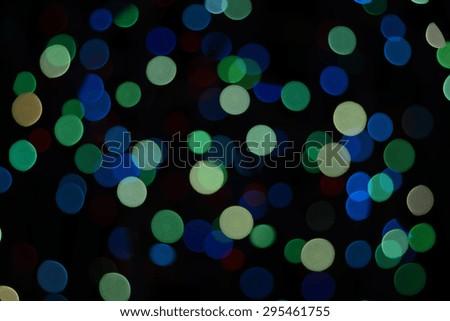 Defocused blue-green lights on the black background - stock photo