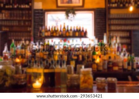Defocused blur of liquor bottles at bar in pub - stock photo