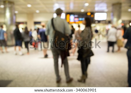 Defocused blur of people waiting at indoor train station - stock photo