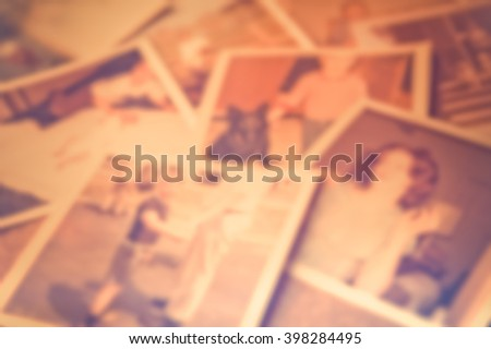 Defocused blur of scattered old family photographs  - stock photo
