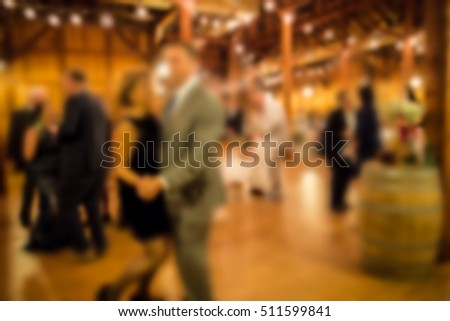 Defocused blur of wedding reception with guests dining and dancing