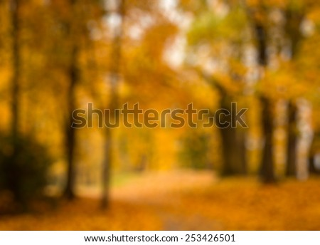 Defocused blurred autum background - valley in fall with yellow tree leaves - stock photo