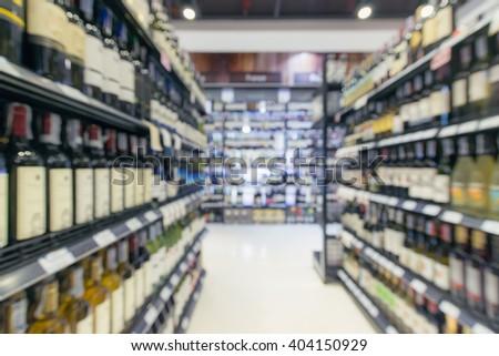 defocused/ Blurred image of bottles of wine on the shelves in supermarket.  - stock photo