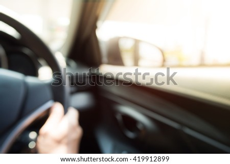 Defocused, blurry of interior car with a hand.