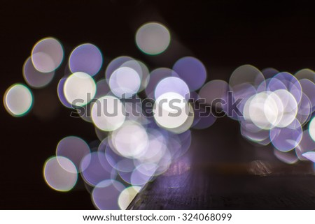 Defocused bokeh Christmas lights on a wooden support - stock photo
