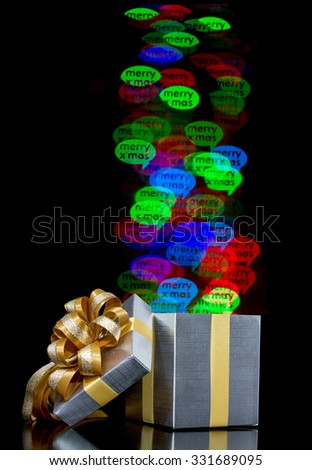 Defocused bokeh lights merry christmas word are moving out of open gift box - stock photo