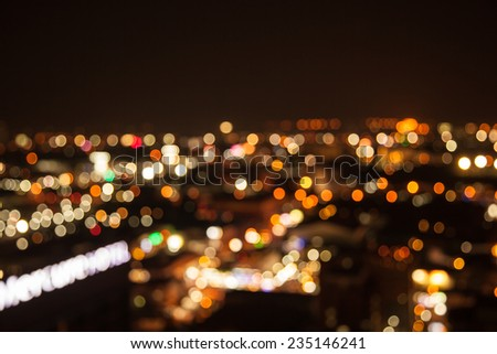 defocused bokeh of light in city on yellow background - stock photo