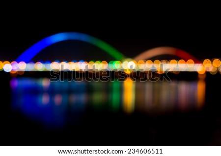 defocused bridge with rainbow color light at night - stock photo
