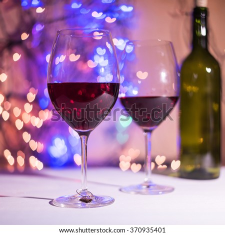 Defocused heart shaped lights bokeh and glasses of wine. Valentine Day concept. Copy space for your text (Dark background) - stock photo