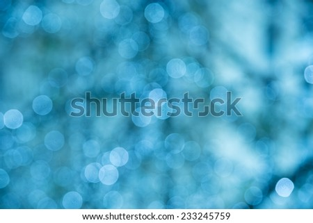 Defocused holiday background with blue tones and sparkle circles - stock photo