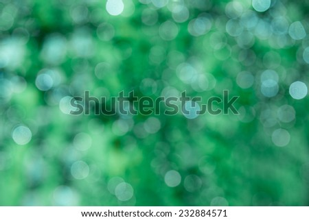 Defocused holiday background with green tones and sparkle circles - stock photo