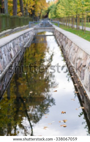 Defocused image of canal with autumnal trees reflection in water, Kadriorg park, Tallinn, Estonia - stock photo