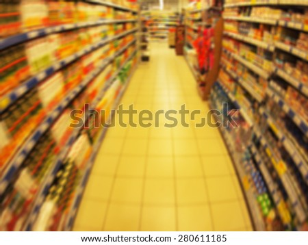 Defocused long shelves of children's goods and products in the supermarket with motion blur