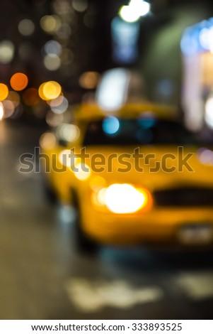Defocused New York City yellow taxi cab blur at night - stock photo