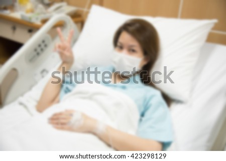 defocused photo blurred background  of asian woman sickness on bed in hospital room but feeling fight
