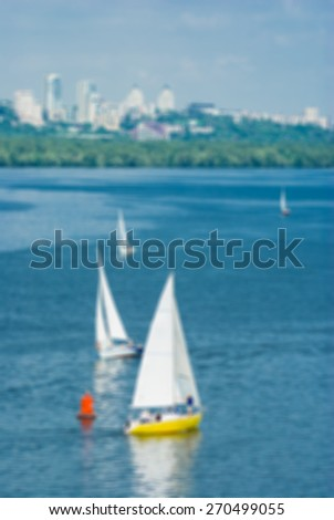 Defocused picture of summer landscape with Dnepr river, yachting and Dnepropetrovsk city skyline, Ukraine - stock photo