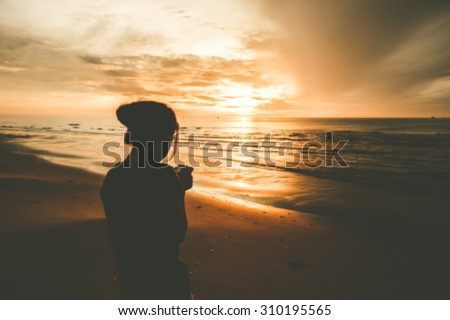 Defocused woman on the beach sunrise.  - stock photo