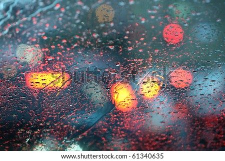 Defocussed traffic viewed through a car windscreen covered in rain, focus on raindrops - stock photo