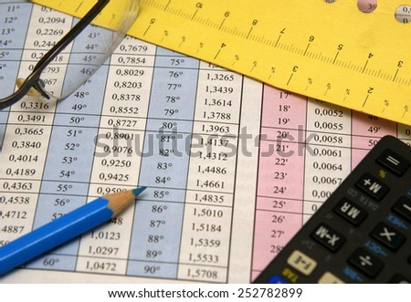 Degrees and radians mathematical table together with glasses, blue pencil, measurement and calculator - stock photo