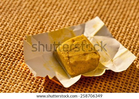Dehydrated bouillon stock cube salty meat and vegetables aromatic yellow spice, ingredient single whole condiment  portion wrapped and open in paper pack on mat, hard daylight, horizontal, nobody.