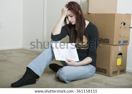 Dejected and sad young red-haired woman sitting on floor of home holding a generic eviction letter in front of cardboard boxes