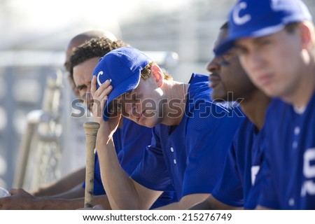 Dejected baseball team, in blue uniform, sitting on bench in stand during competitive baseball game, side view (differential focus) - stock photo