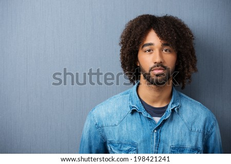 Dejected pensive young African American man standing against a blank chalkboard staring directly at the camera, with copyspace - stock photo