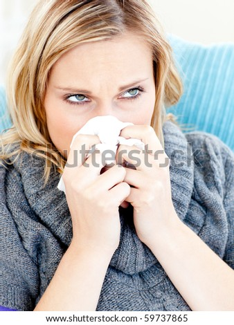 Dejected woman lying on a sofa with tissues and blowing against a white background - stock photo